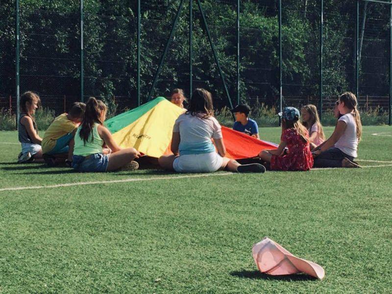 Dzieci siedzące w okręgu i bawiące się kolorowym materiałem